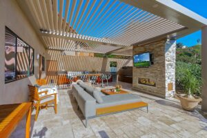 outdoor patio with sitting space and television covered by a pergola