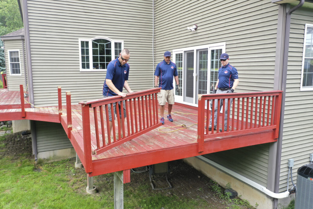 three men in Orange County Deck Company branded shirts demoing an old deck for a rebuild